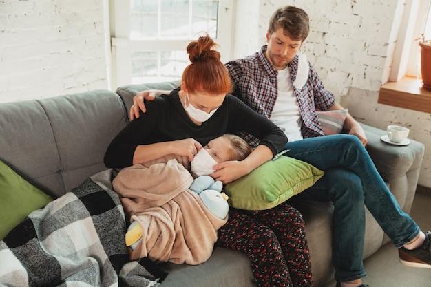 発熱、頭痛、軽度の咳などのコロナウイルス呼吸器症状を伴う自宅で隔離されたフェイスマスクと手袋を着用した白人家族。