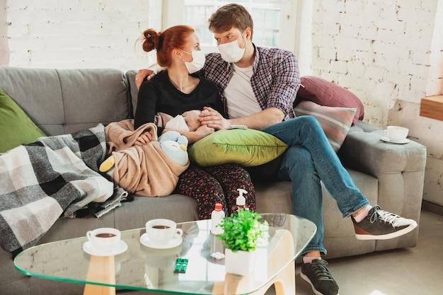 발열, 두통, 가벼운 기침과 같은 코로나 바이러스 호흡기 증상으로 집에서 고립 된 얼굴 마스크와 장갑을 착용 한 백인 가족.
