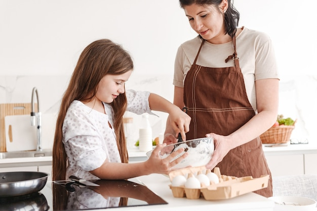 Caucasian family mother and little daughter baking pastry in kitchen at home, and kneading dough with manual mixer