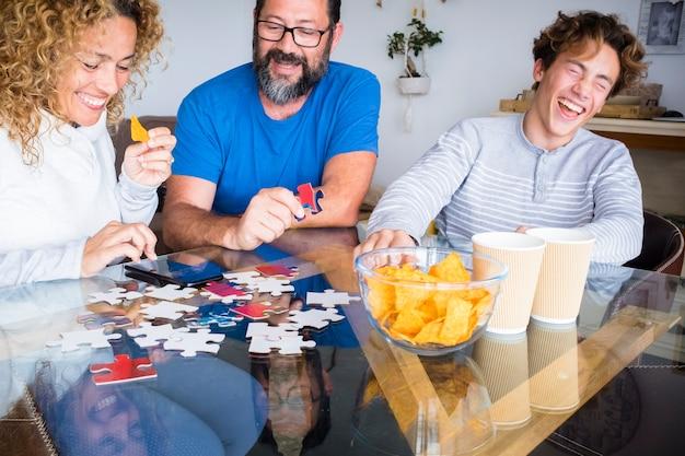 白人の家族は家のテーブルで一緒に遊んで、たくさん笑って楽しんでいます