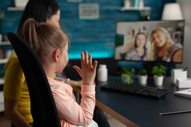 Caucasian family waving at webcam using video call