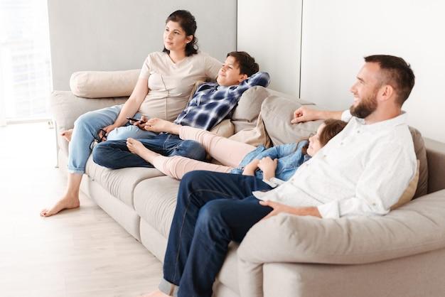 Кавказская семья с двумя детьми отдыхает в гостиной дома и вместе сидит на диване