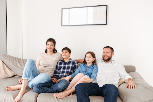 Caucasian family with two children resting in living room at home, and looking at tv together while sitting on sofa