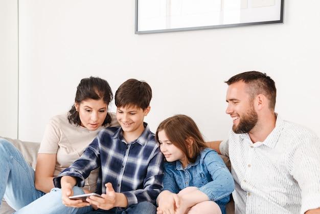 Кавказская семья с двумя детьми сидит на диване вместе дома и использует смартфон