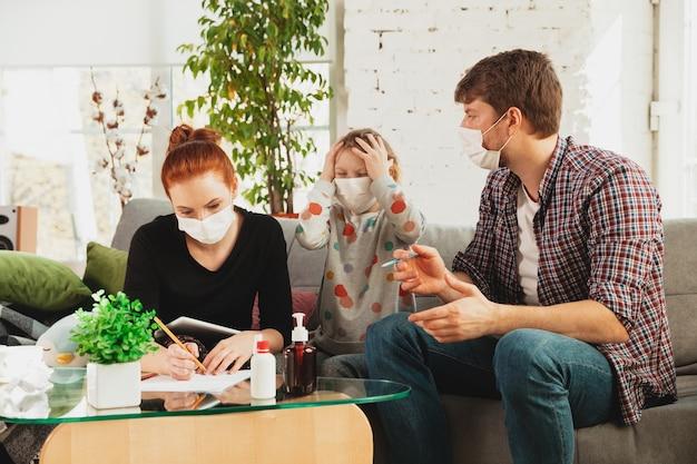 Famiglia caucasica in maschere e guanti isolati a casa con sintomi respiratori del coronavirus come febbre, mal di testa, tosse in condizioni lievi. sanità, medicina, quarantena, concetto di trattamento.