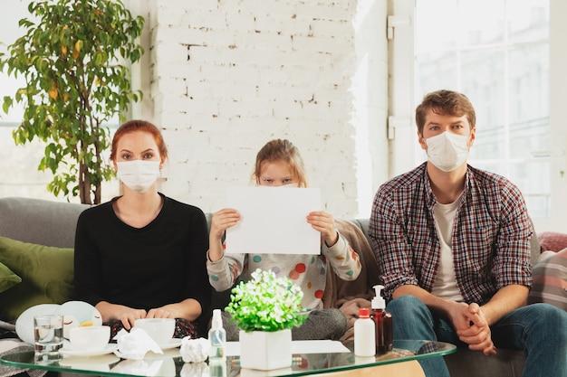 自宅で隔離されたフェイスマスクと手袋を着用した白人家族で、発熱、頭痛、軽度の咳などのコロナウイルス呼吸器症状が見られます。ヘルスケア、医学、検疫、治療の概念。