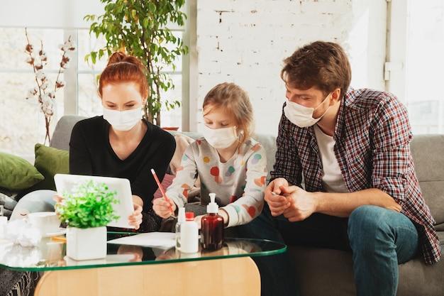 Кавказская семья в масках и перчатках изолирована дома от коронавируса