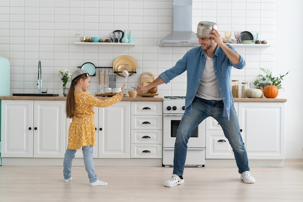 Caucasian father and daughter enjoy battle funny activity in modern kitchen spend active time together on weekend at home Premium Photo