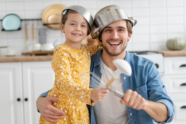 Caucasian father and daughter enjoy battle funny activity in modern kitchen spend active time together on weekend at home