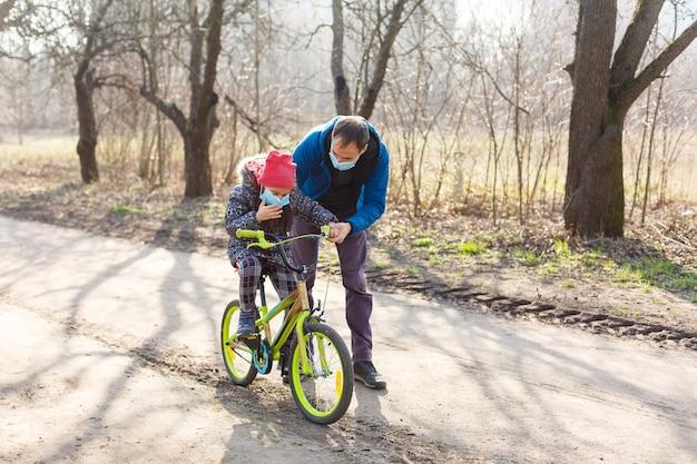 白人の父親は、娘がpm2.5とコロナウイルスcovid-19パンデミックウイルスの症状を保護するための保護マスクを着用して自転車に乗るのを手伝っています。