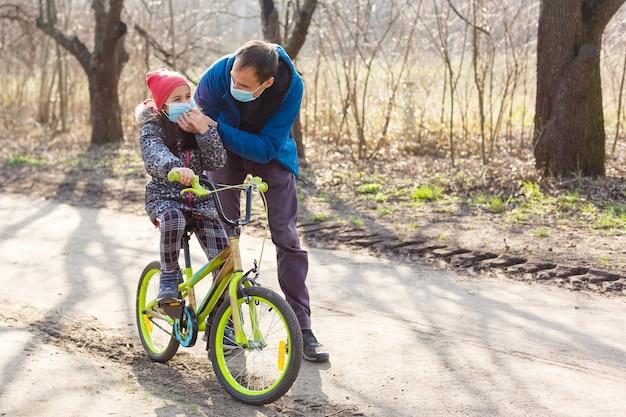 白人の父親は、娘がpm2.5とコロナウイルスcovid-19パンデミックウイルスの症状を保護するための保護マスクを着用して自転車に乗るのを手伝っています。 Premium写真