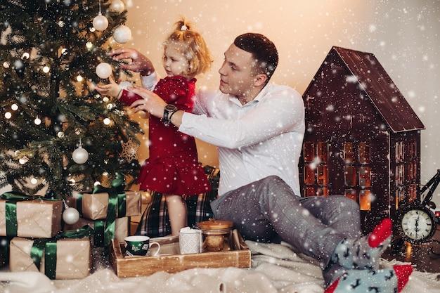 Il padre caucasico aiuta la figlia a decorare l'albero di natale