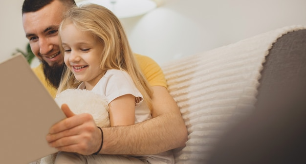 Caucasian father with big beard teaching his girl to read using a book lying on the sofa