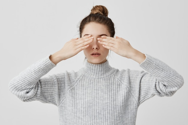 Caucasian female adult 30s with hair in bun covering eyes with both hands. concentrated girl waiting for surprise with closed eyes not know what to expect. body language