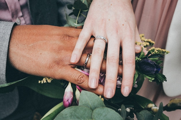 A caucasian female and african american male wearing rings and holding flowersdiversity concept
