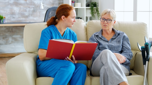 Caucasian female assistant in nursing home reading a book to an elderly retired woman who sits on the couch