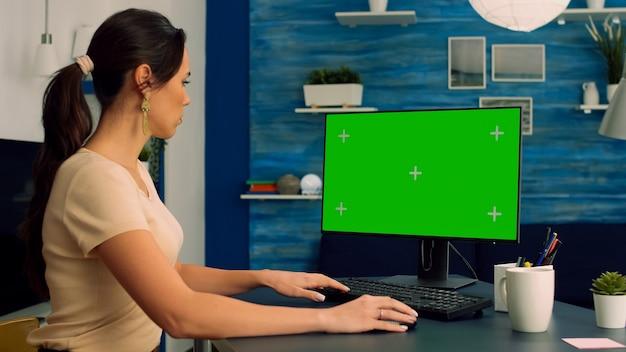 モックアップグリーンスクリーンクロマキーディスプレイとパソコンで作業している彼女の机で白人女性
