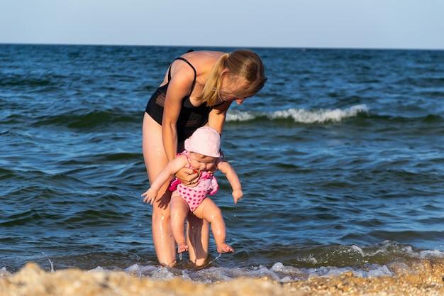 Кавказский ребенок женского пола впервые в море, прыгает в воду и развлекается