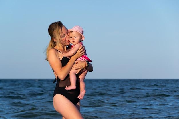 Кавказский ребенок женского пола впервые в море с матерью развлекается