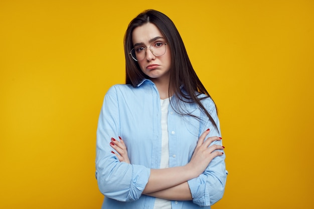 Caucasian female in blue shirt has upset look, frowns face over yellow wall