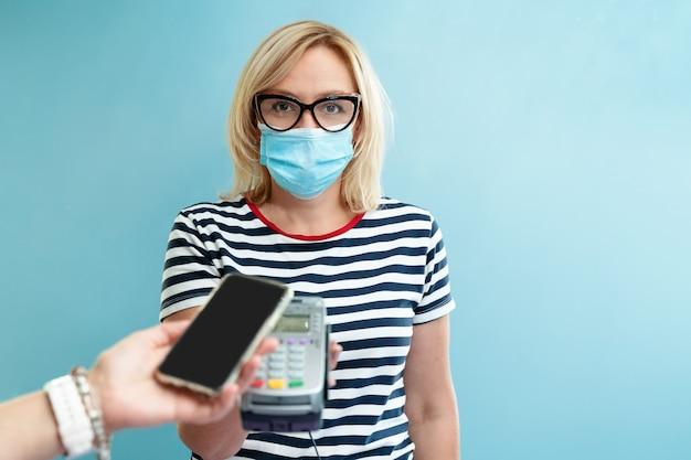 白人女性の事業主は、非接触型スマートフォンで支払いを受けます。