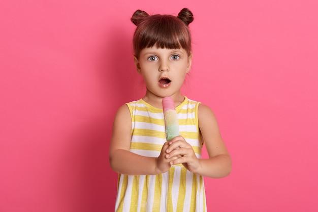 口を大きく開けてポーズをとる白人女性の子は、縞模様の夏のドレスを着て、ショックを受けて、ピンクの壁に大きな目でポーズをとって、驚いて見えます。
