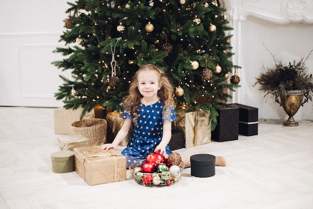 Caucasian female child with boxes with christmas presents