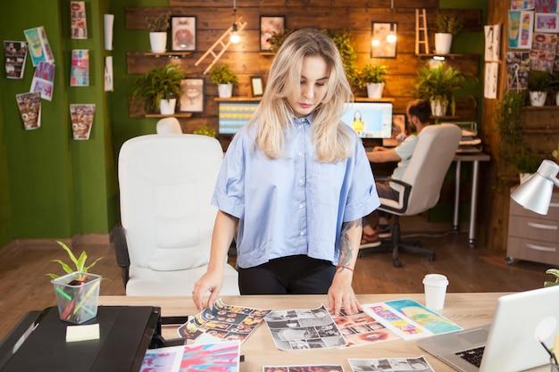 インターンのデザインをチェックする白人女性デザイナー。バックグラウンドでラップトップに取り組んでいる男。