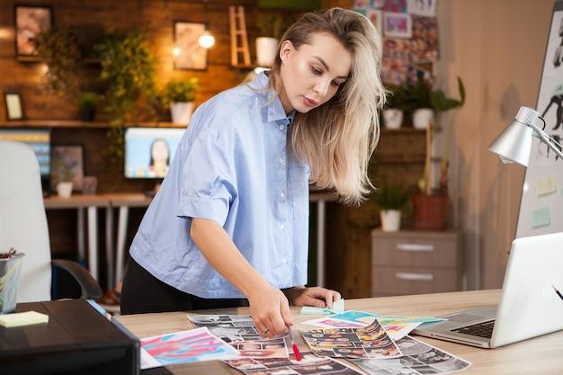 Кавказский женский дизайнер женщина в творческом офисе работает над ее проектами.