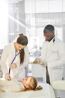 白人の女性医師が聴診器で患者の子供の心拍をチェックし、アフリカの男性の同僚が現代のクリニックで彼女を助けています