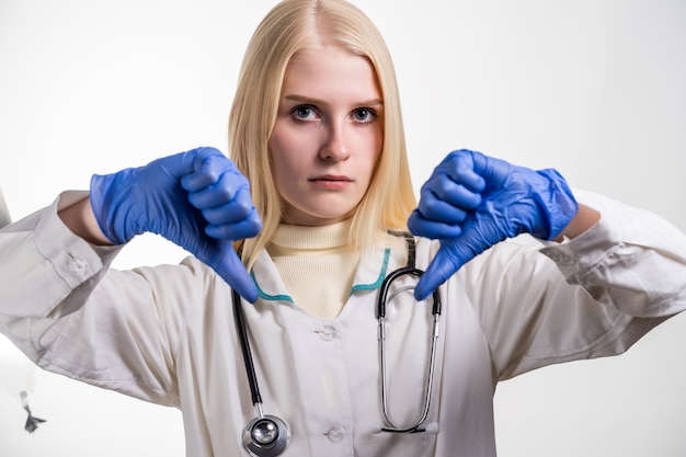Caucasian female doctor showing double thumb down sign or disapprove something