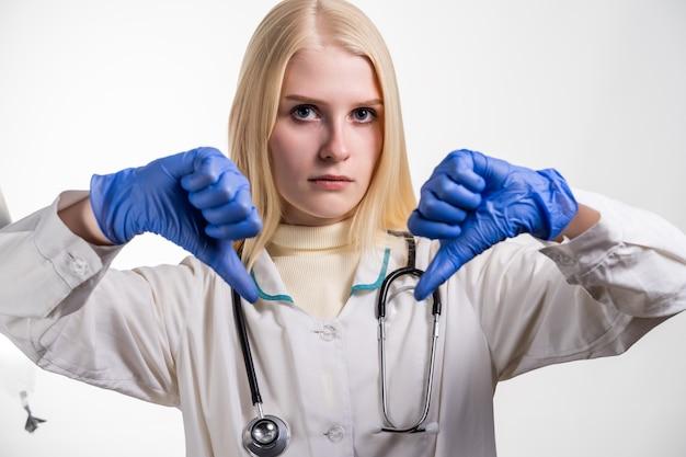 백인 여성 의사 기호 아래로 이중 엄지 손가락을 표시하거나 뭔가 승인