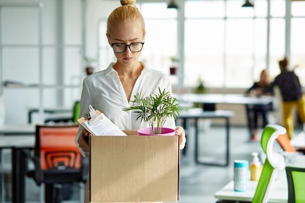 Кавказская женщина-стажер держит картонную коробку с вещами, начинает или заканчивает работу в компании