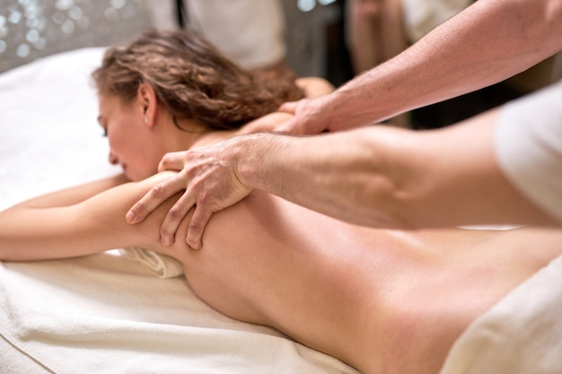 Caucasian female enjoying relaxing full body massage on forearms and cubits in cosmetology spa centre