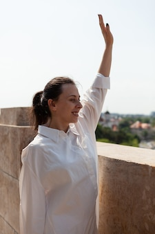 Caucasian female greeting people while standing on tower terrace