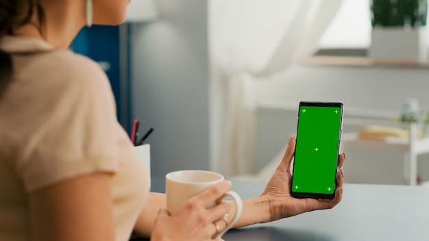 Caucasian female having online videocall using mock up green screen chroma key phone. business woman working at online app using isolated device siiting on office desk in home office