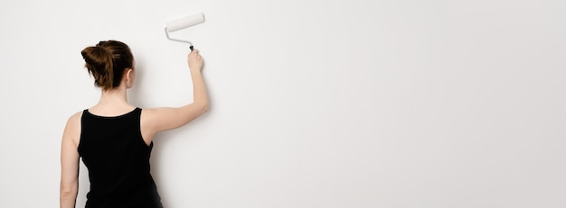 페인팅 롤러를 들고 백인 여성입니다. 롤러 배너와 함께 벽을 그리는 여자