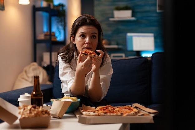 Кавказская женщина держит вкусный кусок пиццы и ест еду на вынос во время просмотра комедии