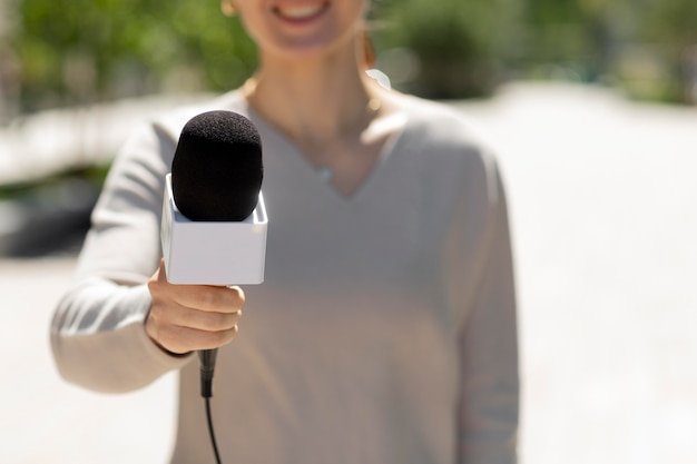 Кавказская женщина-журналист на открытом воздухе