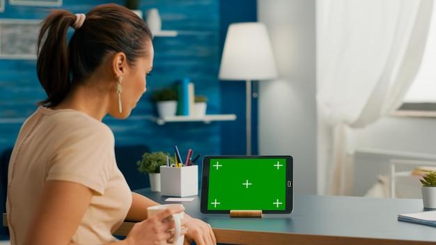 거실에 있는 사무실 책상에 앉아 녹색 화면 크로마 키를 조롱한 태블릿 컴퓨터를 보고 있는 백인 여성. 격리된 장치를 사용하여 소셜 네트워크에서 검색하는 프리랜서 여성