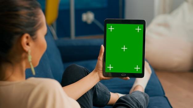 녹색 화면 크로마 키 디스플레이가 있는 태블릿 컴퓨터에서 온라인 회의를 하는 소파에 누워 있는 백인 여성. 소셜 네트워크 탐색을 위해 격리된 터치스크린 장치를 사용하는 여성