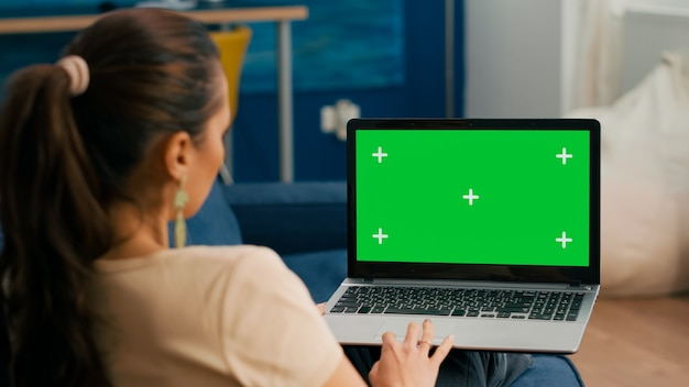 Caucasian female lying on sofa looking at laptop computer with mock up green screen chroma key display. business woman working on financial graphs using isolated pc in home office