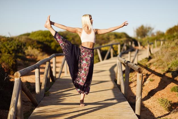 Caucasian female practicing yoga on wooden bridge.