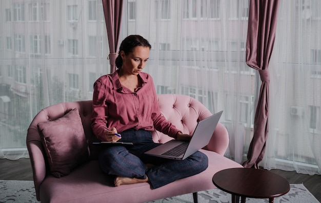 A caucasian female psychologist in a pink shirt is sitting on the couch and working on a laptop