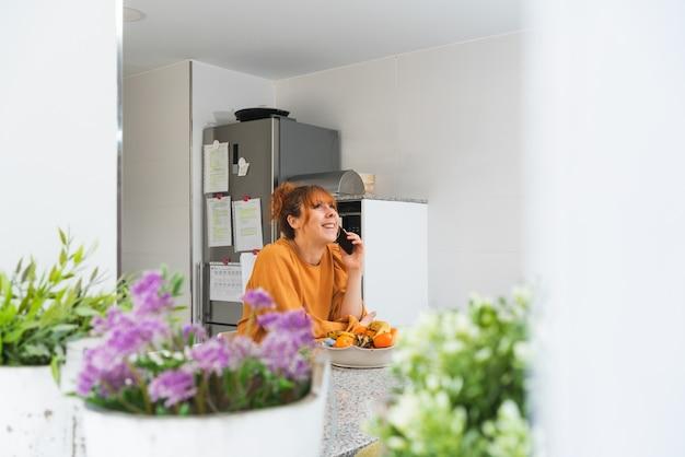 Кавказская женщина рыжая в оранжевой рубашке разговаривает по телефону на кухне