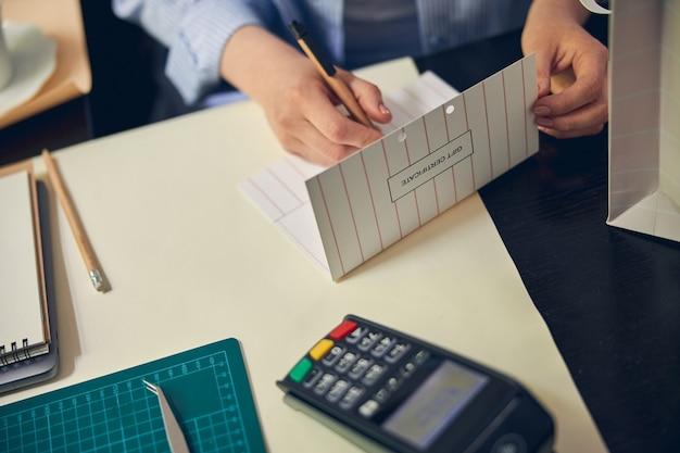Кавказская женщина подписывает личный сертификат для клиентов на деревянном столе