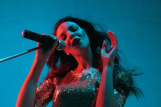 Ritratto di cantante femminile caucasico isolato su sfondo blu studio in luce al neon. bellissimo modello femminile in abito luminoso con microfono. concetto di emozioni umane, espressione facciale, annuncio, musica, arte.