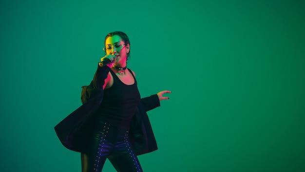 Caucasian female singer portrait isolated on green studio wall