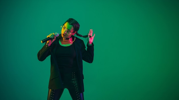 Caucasian female singer portrait isolated on green  wall in neon light. beautiful female model in black wear with microphone. concept of human emotions, facial expression, ad, music, art.