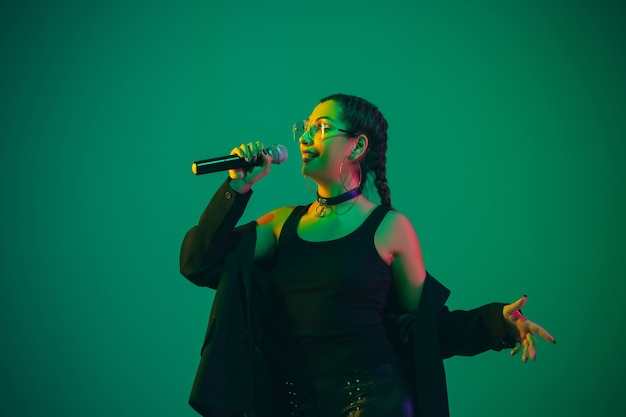 Caucasian female singer portrait isolated on green wall in neon light. beautiful female model in black wear with microphone.